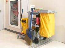 Den rengörande tjänste- vagnen väntar på lokalvård Hink och uppsättning av rengöring royaltyfria foton