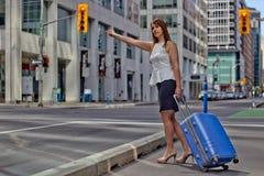 Den resande affärskvinnan välkomnar en taxi i city Royaltyfria Foton