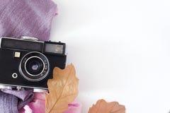 Den Retro kameran och det tomma gamla albumet för ögonblickpappersfoto på den wood tabellen med lönnlöv i höstgräns planlägger -  royaltyfri fotografi