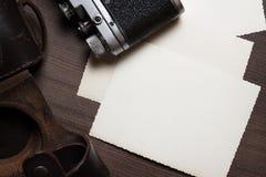 Den Retro kameran och några gammala foto på brunt bordlägger Royaltyfri Foto
