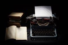 Den Retro skrivmaskinen med bunten av bokar, och öppnad man bokar Royaltyfri Bild