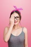 Den Retro utformade unga asiatiska kvinnan täcker henne ögon med en hand Arkivfoton