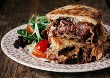 Den Reuben smörgåsen tjänade som med en sida av sallad på en tappningplatta Arkivbilder