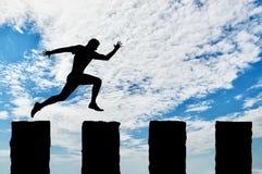 Den rinnande affärsmannen hoppar över klippor Fotografering för Bildbyråer