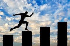Den rinnande affärsmannen hoppar över klippor Arkivfoto