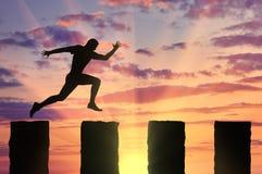 Den rinnande affärsmannen hoppar över klippor Royaltyfri Bild