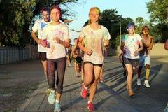 Den rinnande gruppen av tonår och mannen som täckas med pulver, målar Arkivfoto