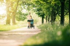Den rinnande kvinnan med behandla som ett barn sittvagnen som tycker om sommar parkerar in Royaltyfria Foton