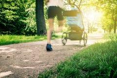 Den rinnande kvinnan med behandla som ett barn sittvagnen som tycker om sommar, rörelsesuddighet Royaltyfria Foton