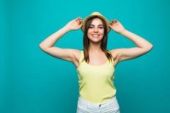 Den roade härliga unga kvinnan i vit sommarkläder, solhatt ser kameran som är upphetsad på grön bakgrund arkivfoton