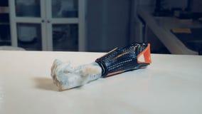 Den Robotic armen ligger på tabellen och de rörande fingrarna Verkligt robotic människa-som armen lager videofilmer