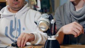 Den Robotic armen tar en can Verklig robotic arm i arbete arkivfilmer