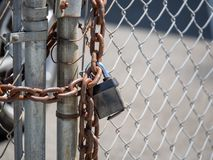 Den robusa kedjan slår in ett staket för chain sammanlänkning som är stängt med en hänglås royaltyfri bild
