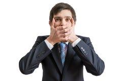 Den roliga affärsmannen täcker hans mun med händer bakgrund isolerad white Arkivfoton