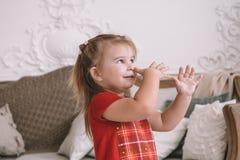 Den roliga barnflickan spelar hemma flicka som har gyckel och att dansa hemmastadda rekreation och underhållning royaltyfri fotografi