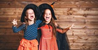 Den roliga barnsystern kopplar samman flickan i häxadräkt i halloween royaltyfri fotografi