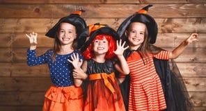 Den roliga barnsystern kopplar samman flickan i häxadräkt i halloween arkivfoton