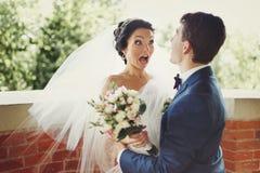 Den roliga bruden ser chockat som kramas av en brudgum Fotografering för Bildbyråer