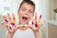 Den roliga caucasian pojken med målade händer visar dem på kameran, joyf royaltyfria bilder
