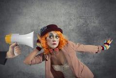 Den roliga clownen hör en megafon med ett meddelande arkivfoton