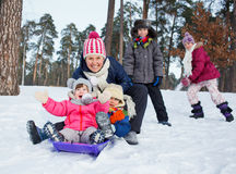 Den roliga familjen åka släde i vinter-landskap Arkivfoto