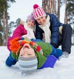 Den roliga familjen åka släde i vinter-landskap Royaltyfri Foto