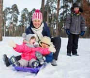 Den roliga familjen åka släde i vinter-landskap Royaltyfria Bilder