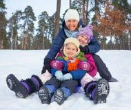 Den roliga familjen åka släde in vinter-landskap Arkivbilder