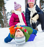 Den roliga familjen åka släde in vinter-landskap Royaltyfri Foto