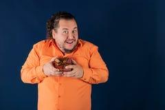 Den roliga feta mannen i orange skjorta öppnar en ask med en gåva arkivbild