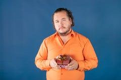 Den roliga feta mannen i orange skjorta öppnar en ask med en gåva royaltyfri bild