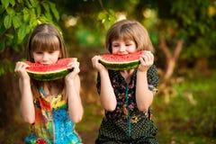 Den roliga flickan för små systrar äter vattenmelon i sommar arkivfoto