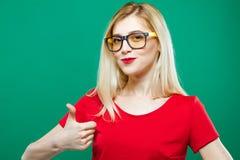 Den roliga flickan i glasögon visar tummen upp på grön bakgrund Härlig blondin med långt hår och den röda överkanten i studio Arkivfoto