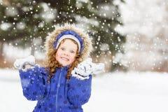Den roliga flickan lyftte hennes händer i luften som fångar snowf Arkivbilder