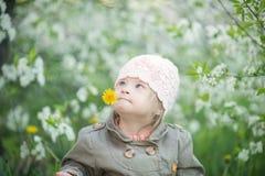 Den roliga flickan med Down Syndrome i munnen drar maskrosor Fotografering för Bildbyråer