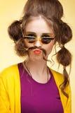 Den roliga flickan med fejkar mustaschen Royaltyfria Bilder