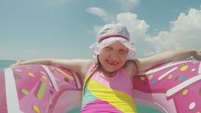 Den roliga flickan på en rosa uppblåsbar cirkel och i en rolig panamka för barn` som s solbadar i solen som rullar på havet, vink stock video