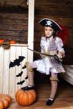 Den roliga flickan piratkopierar in dräkten i studion med landskap för allhelgonaafton Royaltyfria Bilder