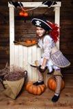 Den roliga flickan piratkopierar in dräkten i studion med landskap för allhelgonaafton Royaltyfri Bild