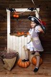 Den roliga flickan piratkopierar in dräkten i studion med landskap för allhelgonaafton Arkivbild