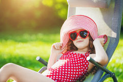 Den roliga flickan solbadar på en soldagdrivare Arkivbild