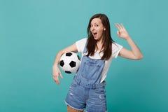 Den roliga fotbollsfan för den unga kvinnan hurrar upp det favorit- laget för service med fotbollbollen som visar reko gest som i royaltyfri fotografi