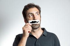 Den roliga grabben med fejkar mustaschen Fotografering för Bildbyråer