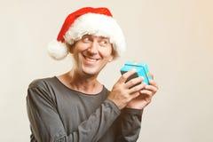 Den roliga grabben med julhatten rymmer liten gåva Ferie för nytt år Jul x-mas, vintergåvabegrepp Man som bär Santa Clau arkivfoto