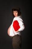 Den roliga gravida Caucasian brunetten i en skjorta, lock, flåsar byx- Arkivfoto