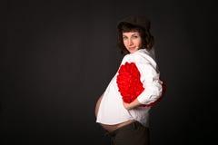 Den roliga gravida Caucasian brunetten i en skjorta, lock, flåsar byx- Royaltyfria Foton