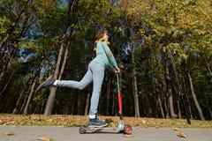 Den roliga gravida kvinnan rider sparkcykeln i parkera Fotografering för Bildbyråer