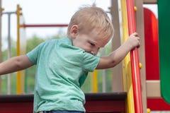 Den roliga gulliga caucasian blondinen behandla som ett barn pojkelekar på lekplatsen som klättrar till upstair royaltyfria bilder