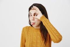 Den roliga gulliga caucasian flickan som ut klibbar tungan och bra visar, undertecknar över ögat, medan se till och med det som,  royaltyfri bild