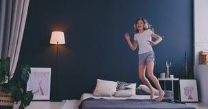 Den roliga gulliga lilla flickan i tr?dl?s h?rlurar som dansar att sjunga med h?rkammen och, har gyckel i feriemorgonbanhoppning  stock video